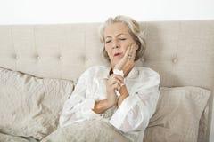 遭受牙痛的资深妇女休息在床上 免版税库存照片