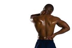 遭受痛苦的赤裸上身的运动员背面图 免版税库存照片