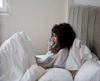 遭受的妇女在床上 库存图片