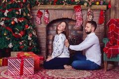 遭受肩膀痛苦的他怀孕的妻子的丈夫按摩 免版税库存图片