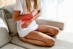 遭受胃痛的妇女,在家坐沙发 免版税库存图片