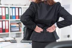 遭受背部疼痛的女实业家 免版税库存图片