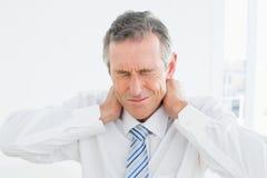遭受脖子痛的一个成熟人的特写镜头 免版税库存图片