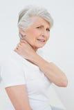 遭受脖子痛的一名资深妇女的侧视图画象 库存照片