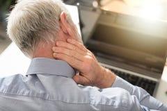 遭受脖子痛,光线影响的商人 免版税库存图片