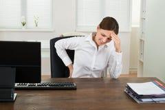 遭受腰疼和头疼的女实业家 免版税库存照片