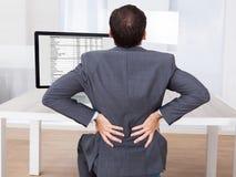 遭受腰疼的商人,当坐在书桌时 免版税库存图片