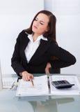 遭受腰疼的税务顾问在书桌 免版税库存图片