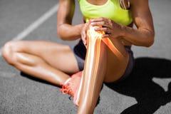 遭受膝盖痛苦的女运动员的低部分 图库摄影