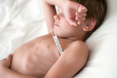 遭受说谎与在腋窝的一个温度计的疾病孩子 免版税库存图片