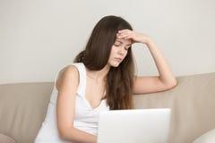 遭受头疼的夫人在膝上型计算机的工作以后 免版税库存图片