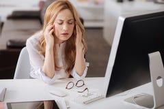 遭受头疼的沮丧的年轻办公室经理在工作场所 免版税库存图片