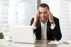 遭受头疼的疲乏的商人 免版税库存图片