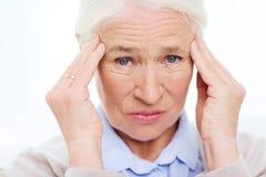 遭受头疼的资深妇女的面孔 免版税库存图片