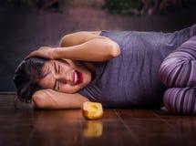 遭受anorexy,尖叫和放置在与她的胳膊的木地板上的美丽的女孩在她的顶头痛苦附近 免版税图库摄影