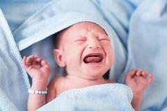 遭难哭泣在一块蓝色毛巾的浴以后的新出生的婴孩 库存图片