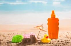 遮光剂、沙堡、伞和儿童` s戏弄onseashore 库存照片