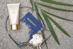遮光剂,玻璃,壳,在沙子的棕榈叶 免版税图库摄影