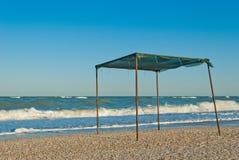 遮篷眺望台机盖由布料和金属制成,以海和天空为背景 免版税库存照片