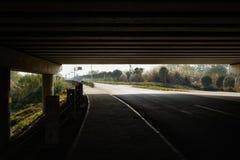 遮荫涂柏油的路在高速公路射线桥梁下在晴朗的冬天 免版税库存照片