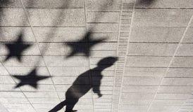 遮蔽一个男孩的剪影城市边路的 免版税库存图片