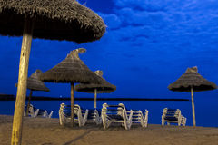 遮阳伞和海滩懒人在月光海滩 库存图片