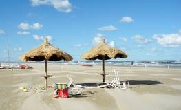 遮阳伞和轻便折叠躺椅在海滩 库存照片
