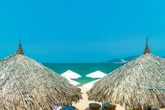 遮阳伞稻草屋顶在海滩的在南海附近 库存图片