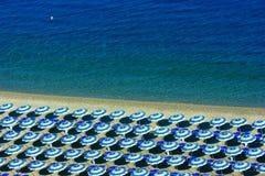 遮阳伞行在海滩的 免版税库存照片