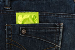 避孕套品种在蓝色牛仔裤的 免版税库存照片