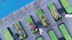 避暑胜地,可爱的愉快的女性朋友到放松在轻便折叠躺椅的泳装里在昂贵的手段的水池附近在期间 股票视频