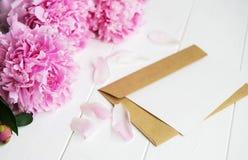 邀请卡片、工艺信封和桃红色牡丹开花 免版税库存图片