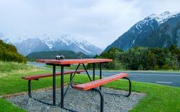 邀请的表和长凳在雪山山脉的脚 免版税图库摄影