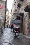 那不勒斯,意大利- 2018年11月04日, 年轻人骑马摩托车在伞下在雨中 库存图片