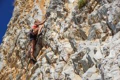 那不勒斯,意大利2017年9月-04 :一名未认出和运动妇女在海附近攀登山在一个热的夏天 库存照片