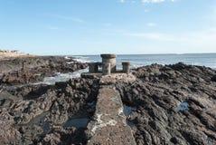 那导致一张具体桌和椅子在一个孤立海滩的道路 库存照片