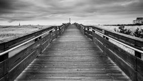 那导致天际由在大绿色高草地上的天际在风雨如磐的天空下的黑白木桥梁 免版税库存照片