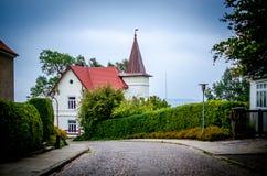 那导致美丽的斯堪的纳维亚房子在海边前面的路 库存图片