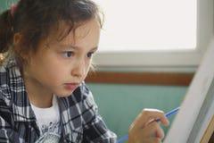 那的女孩与一把刷子的油漆在帆布 图库摄影