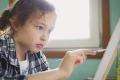 那的女孩与一把刷子的油漆在帆布 免版税库存图片