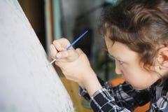 那的女孩与一把刷子的油漆在帆布 库存照片