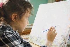 那的女孩与一把刷子的油漆在帆布 库存图片