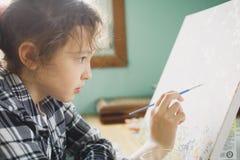 那的女孩与一把刷子的油漆在帆布 免版税图库摄影