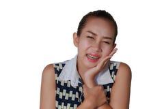 那里亚裔妇女是许多有头疼和牙痛在白色背景的畸齿矫正术以后 库存照片