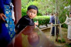 那霸,日本- 11月19 :传统衣裳的年轻男孩在公园看2015年11月19日的照相机在那霸,日本 免版税库存图片