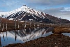 那Majesctic Pyramida的山耸立在被放弃的俄国鬼城Pyramiden在斯瓦尔巴特群岛 库存照片