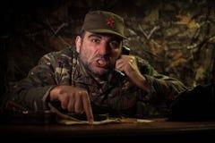邪恶的独裁者坐桌 在总部或古巴司令员的恼怒的共产主义一般开会在暗室 免版税库存图片