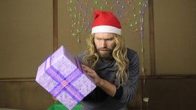 邪恶的矮人或坏拿着在庆祝的包装的圣诞老人一件礼物 股票录像