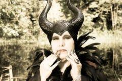 邪恶的童话、有害,恶劣女王/王后有垫铁的和乌鸦用羽毛装饰褂子 免版税库存图片
