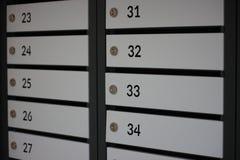 邮件、小包和信件的分类收集和报纸的编号箱在一个多层的大厦 有锁的箱子 库存照片